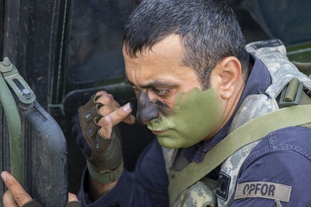 An Azerbaijan soldier, with the Azerbaijan Peace Keeping Company, applies face paint during the occupation of a simulated town during Saber Junction 2019, at the Joint Multinational Readiness Center in Hohenfels Germany, Sept. 25, 2019. Saber Junction 19 (SJ19) is an exercise involving nearly 5,400 participants from 16 ally and partner nations. SJ19 is designed to promote interoperability with allies and partner nations.