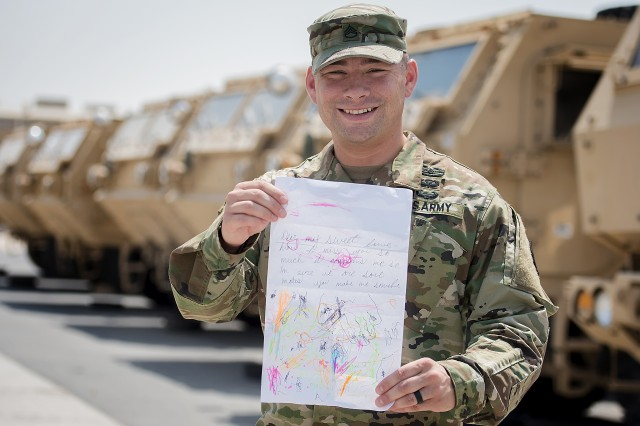 Staff Sgt. James Cornejo, quality assurance, 401st Army Field Support Battalion-Qatar, shows off a correspondence he received from his family while standing outside the motor pool at Army Prepositioned Stocks-5, Sept. 16, Camp As Sayliyah, Qatar. He said staying in contact with his wife and children helps to keep him focused on his job, which is to ensure the readiness of equipment at APS-5.