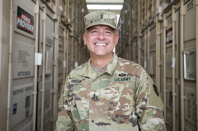 "Chief Warrant Officer 4 Vicente Rivera, supply systems technician, 401st Army Field Support Battalion-Qatar, stands between rows of Force Provider storage containers at Army Prepositioned Stocks-5, Sept. 16, Camp As Sayliyah, Qatar. Rivera said Force Provider systems are ""like a city in a box,"" and can be used for temporary encampments."