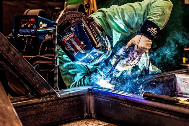Welder Josh Miller welds the frame assembly for a Power Equipment Group (PEG) pallet. The new build PEG pallet is still in low rate initial production while the customer adjusts the design to meet the needs of the warfighter.  The majority of the PEG is raw stock metal, welded and then painted.