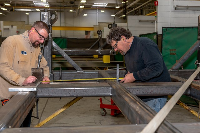 Left, Welder Josh Miller and Welding Worker Bill Prebish, measure the PEG pallet frame assembly to mark the location of the cross beam. The welders work in the Systems Integration and Support Directorate's Welding Branch.