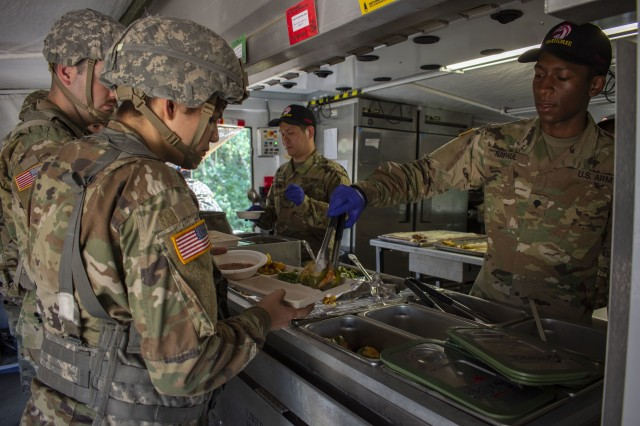Army Private First Class Woo Lee and Spc. Matthew Naipaul assigned to Foxtrot Company, 427th Brigade Support Battalion, New York National Guard from Farmingdale, N.Y., serve food during the Connelly Competition at Fort Drum, N.Y., July 26, 2019. The Philip A. Connelly Awards Program recognizes excellence in Army Food Service and is named after Philip A. Connelly, former president of International Food Service Executives Association (IFSEA). The program is run by the Army and the National Restaurant Association.
