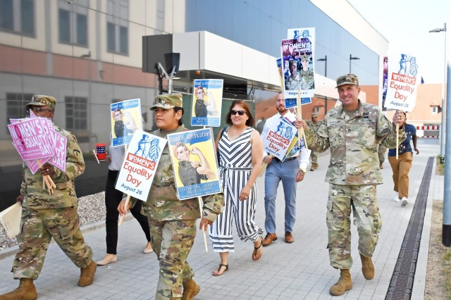 Then-acting Garrison Command Sergeant Major 1st Sgt. Lori Soto and Sgt. 1st Class Brett Hartley walk together with several community members to the Women's Equality Observance in the fitness center Aug. 26.