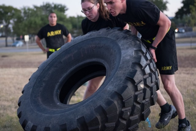 Capt. Emily Shinogle and Capt. Timothy Ruiz, 13th Expeditionary Sustainment Command, use teamwork to flip a tire Sept. 25 during a team building event.  During the 13th ESC's birthday week Sept. 24-27, events included esprit de corps activities such as a Family fun run, cake cutting ceremony, Commander's Cup competition, golf tournament and wreath laying ceremony.  (U.S. Army photo by Sgt. 1st Class Kelvin Ringold)