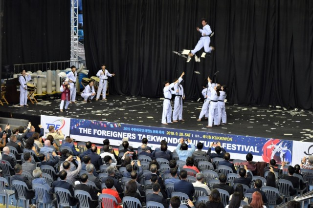 A Taekwondo demonstration team shows how teamwork and training can break boards even high above the ground during the opening ceremony at the 2019 Foreigners Taekwondo Culture Festival at Kukkiwon Taekwondo Headquarters in Gangnam, Seoul, South Korea, Sept. 28. Eighth Army Soldiers joined fellow Taekwondo-ins for the annual event.