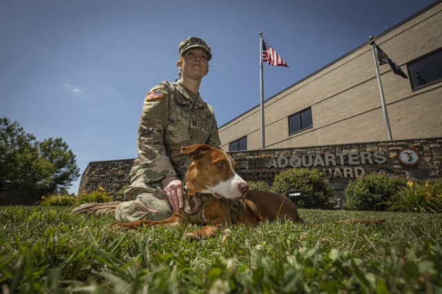 U.S. Army Capt. Melissa Parmenter and therapy dog Ace sit for a portrait in front of the New Jersey National Guard's Joint Force Headquarters on Joint Base McGuire-Dix-Lakehurst, N.J., Aug. 12, 2019. Parmenter and Ace are both part of the New Jersey Army National Guard's Behavioral Health Office.