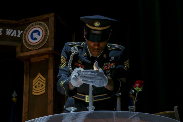 Sgt. 1st Class Anthony Bynum, material manager, support operations (SPO), 1st Theater Sustainment Command (TSC), prepares to light a candle at the Prisoner of War/Missing in Action (POW/MIA) table during the 1st TSC noncommissioned officer (NCO) induction ceremony on Sept. 30, 2019 at Olive Theater, Fort Knox, Ky. The table recognizes those members that are missing and honors their memory and service. (U.S. Army photo by Spc. Zoran Raduka).