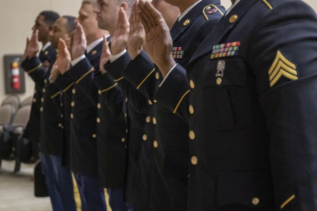 Newly inducted noncommissioned officers (NCOs) raise their hand and swear to accept the responsibilities of the NCO during the 1ST Theater Sustainment Command (TSC) induction ceremony held Sept. 30, 2019 at Olive Theater on Fort Knox, Ky.