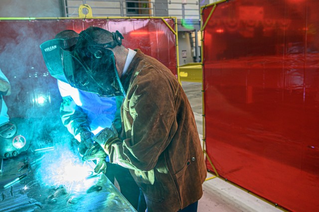Army Col. Jared Helwig, U.S. Army Chief of Transportation performs ceremonial welds in a ceremony marking the keel laying of the Army's newest watercraft, the Maneuver Support Vessel (Light) in Vancouver, Wa. on Sept. 16, 2019.