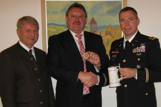 Franz Zeilmann, community and media relations specialist, U.S. Army Garrison Bavaria (left) joins Mayor Hans-Martin Schertl, City of Vilseck (center) and Col. Mark Colbrook, former commander, USAG Bavaria for a photo during an engagement, Oct. 14, 2014. Zeilmann has served as a liaison between between the U.S. Army and German leadership for more than 27 years. (Photo provided by USAG Bavaria Public Affairs)