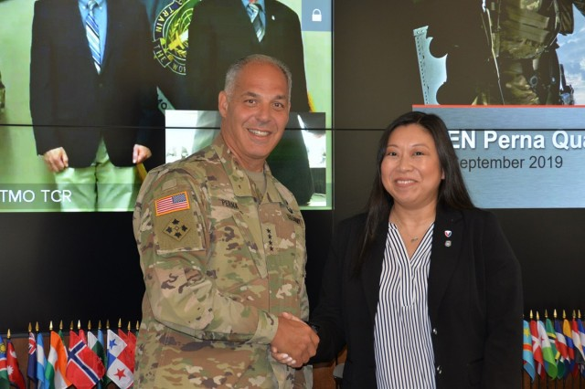 Army Materiel Command's Commander Gen. Gus Perna presents a commander's coin to Summer Paquette during his quarterly visit to U.S. Army Security Assistance Command. Paquette is the country program manager to Brazil, overseeing foreign military sales to the country.