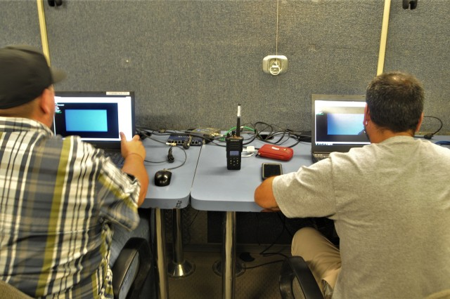 Behind each camera set up on a test, is a high-speed technician who is monitoring it via a live video feed shown on a camera controller from inside a support test vehicle. Sean Mynster, high-speed video test lead (right) and Steven Mowery, high-speed technician (left) are shown monitoring a test site.