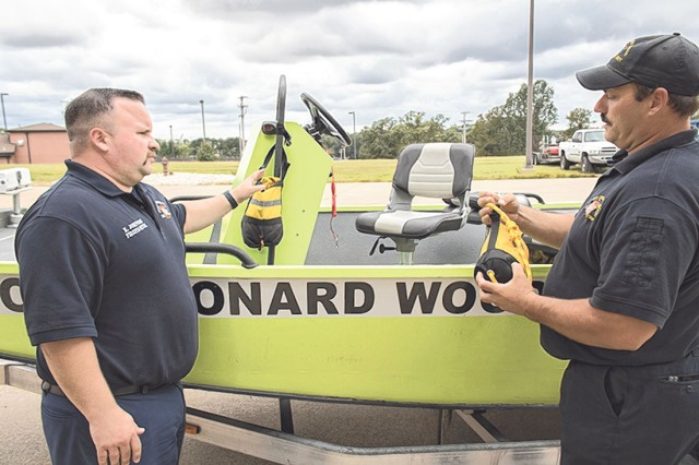 Firefighter Kyle Johnson, boat operator (left), talks rope procedures with Fire Capt. Bryan West alongside the boat used to rescue the five victims in the Gasconade River Sept. 15.