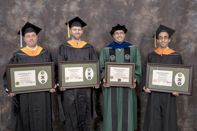 A Picatinny employee was presented the first Armament Graduate School Doctor of Philosophy in Armaments Engineering certificate on Oct. 3, while three other employees received Master of Armament Engineering certificates during the school's fifth commencement ceremony. From left, Nathan M. Peabody, Jonathan H. Copp, Tomas R. Bober and Steven, L. Manole show their certificates. Bober was the first student to receive a doctorate from the school.