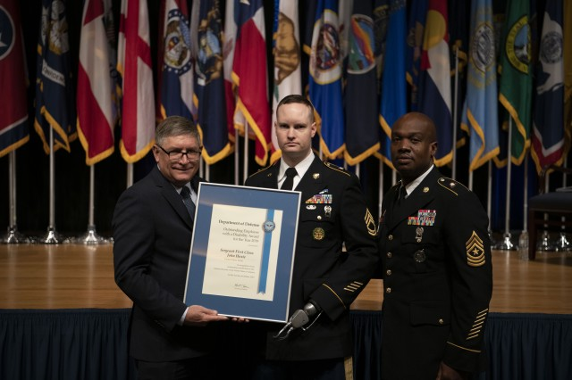 Sgt. 1st Class John C. Hoxie, center, senior geospatial intelligence imagery analyst at Army South Command, Fort Sam Houston, Texas, is recognized at the 39th Annual Secretary of Defense Disability Awards Ceremony in the Pentagon, Oct. 3, 2019.