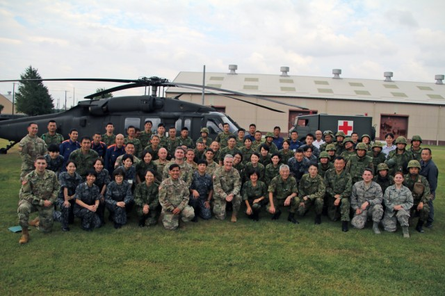 SAGAMIHARA, Japan - Medical personnel with U.S. Army Medical Department Activity-Japan; U.S. Air Force 374th Medical Group; Japan Ground Self-Defense Force; Japan Air Self-Defense Force; and Sagamihara Fire Bureau gather for group photo by the UH-60L Black Hawk Helicopter and JGSDF Medical Evacuation vehicle during Tactical Combat Casualty Care training at Sagami General Depot, Oct. 3. MEDDAC-J hosted TCCC training Sept. 30 through Oct. 3 to improve medical capabilities and interoperability amongst both JGSDF and U.S. Army medical Soldiers.