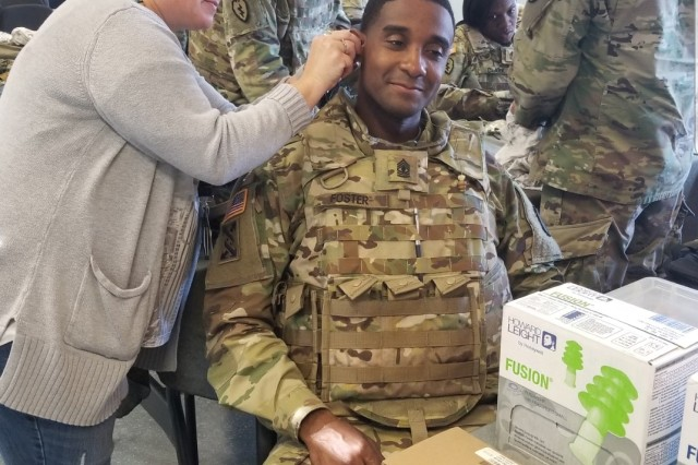 Ms. Michelle Opse, a hearing technician in the Hearing Conservation clinic at Landstuhl Regional Medical Center, fits 1st Sgt. Willie Foster of Headquarters and Headquaters Company, 21st Special Troops Battalion, 21st Theater Sustainment Command, with hearing protection during a weapons qualification at Breitenwald range, Sept. 11.