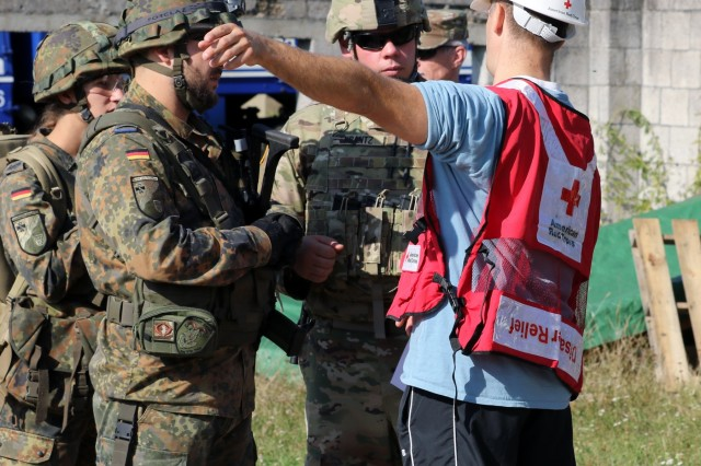 Capt. Jess Krantz, civil affairs team chief, with 457th Civil Affairs Battalion, 361st Civil Affairs Brigade, Kaiserslautern Germany, out of Wackernheim Germany and Soldiers of the German Bundeswehr, receives information from a member of the American Red Cross during exercise Cobra Strike 2019, in Wackernheim, Germany Sept. 14, 2019. Cobra Strike is a multinational, multiorganizational field training exercise in humanitarian assistance in collaboration with the Bundeswehr, THW, American Red Cross. (U.S. Army Reserve Photo by Sgt. Christopher Stelter).