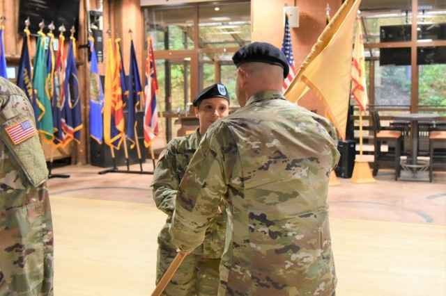 Capt. Stephanie R. Correa passes the guidon to U.S. Army Garrison Rheinland-Pfalz Commander Col. Jason T. Edwards to relinquish command of the Headquarters, Headquarters Company at a change of command ceremony Oct. 4 at Kazabra Club. Capt. Sebastian D. Armentrout is the new company commander.