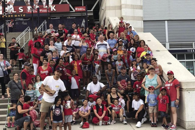 Fort Belvoir Elementary and Upper School staff pose with students and parents in front of Nationals Park, before catching the last regular-season game. The MLB franchise provided 2,000 tickets to the installation's children as a reward for their schools being selected as Grand Slam Schools.