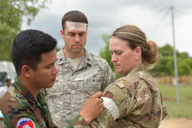 A  member of the Royal Cambodian Armed Forces writes a notional injury on Idaho Air National Guard Airmen Tech. Sgt. Kelly Goodman as part of a first aid expert exchange at the United Nations Peace Keeping Operations center in Cambodia Sept. 18. The mission was part of the National Guard's State Partnership Program and included a team of four Idaho Army National Guard Soldiers and two 124th Fighter Wing Airmen. Soldiers and Airmen spent the week training with members of Cambodia's peacekeeping directorate who are preparing to deploy to several countries as part of the National Center for Peacekeeping, Mines, and Explosive Remnants of War Clearance program. More than 70 NPMEC Soldiers made up three groups consisting of an engineer, medical and leadership engagements.