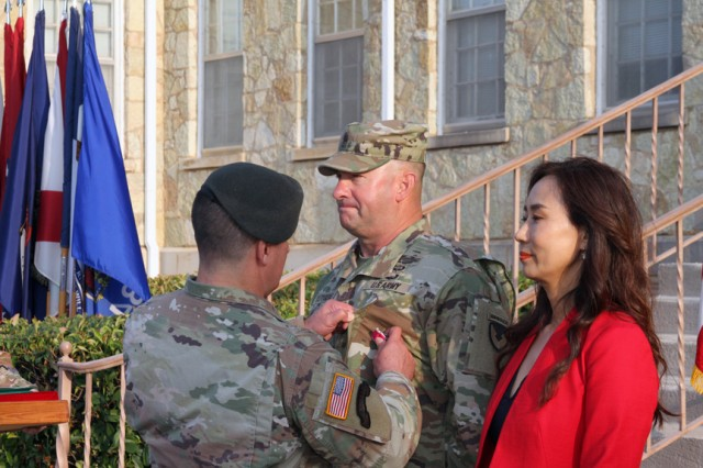 Col. Don King Jr., Fort Sill Garrison commander, pins the Legion of Merit on garrison Command Sgt. Maj. Jonathan Lutgens during an award ceremony Oct. 4, outside Taylor Hall. Lutgens retired with over 30 years of service. Lutgens, and his wife, Grace, right, will relocate to Texas.