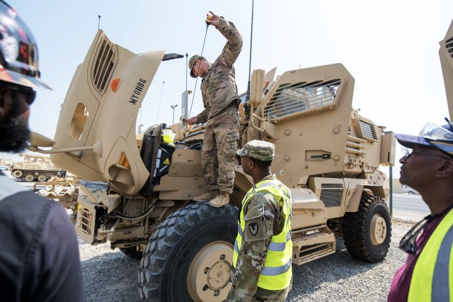 Sgt. 1st Class Roy Carson (center), maintenance quality assurance for wheeled vehicles, 401st Army Field Support Battalion-Kuwait, approaches Sgt. Matthew Molden, Chaos Company, 1st Battalion, 68th Armor Regiment, 3rd Army Brigade Combat Team, 4th Infantry Division, as the Soldier checks the fluid levels of a MaxxPro Mine-Resistant Ambush Protected (MRAP) vehicle during an issue of equipment to the unit from Army Prepositioned Stocks-5, Camp Arifjan, Kuwait, Oct. 3. Carson was checking on a reported deficiency with the vehicle with maintenance contractor support nearby to help correct any verified problem.