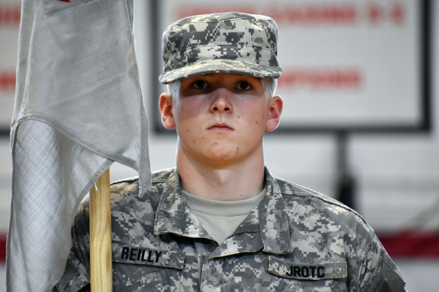 Cadet Pvt. Joshua Reilly, a member Company B, Trojan Battalion of the Junior Reserve Officers' Training Corps at Zama Middle High School, bears his company's guidon during a promotion ceremony at the school, Camp Zama, Japan, Oct. 3.