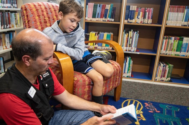 Christopher Bowen, a Red Cross volunteer, helps Patrick read aloud at the Wiesbaden Library in Clay Kaserne, Wiesbaden, Germany, October 2, 2019. Bowen gives back to his community through this event and many others including hospital visits. (U.S. Army Photo by Pfc. Laurie Ellen Schubert, 5th Mobile Public Affairs Detachment)