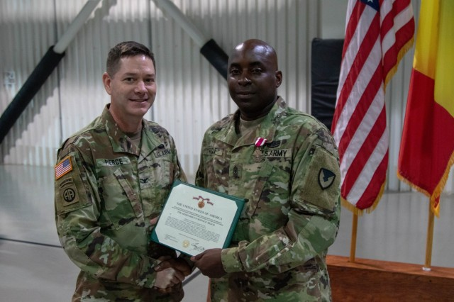 Sgt. Maj. Matakiah Fogle Jr., the outgoing garrison sergeant major of Mihail Kogalniceau Air Base in Romania, receives the Meritorious Service Medal from Col. Steven Pierce, the commander of U.S. Army Garrison Ansbach, before his change of responsibility ceremony on Oct. 3, 2019. During the ceremony, Fogle transferred the duties and responsibilities of the garrison to the incoming Sgt. Maj. Gary J. Williams. MK AB is a permanent forward operating site and can support over 1600 service members at a given time. (U.S. Army photo by Spc. Ethan Valetski, 5th Mobile Public Affairs Detachment)