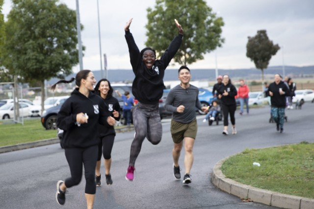 A participant in the Take Back the Night Run and Walk leaps in the air as she runs along the route of the race on Clay Kaserne, Wiesbaden, Germany, Oct. 3, 2019. The event was designed to bring the community together to highlight the importance of a safe and respectful environment.  (U.S. Army photo by Sgt. Erica Earl)