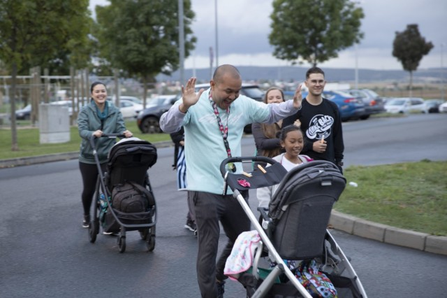 A participant pushes a child in a stroller at the Take Back the Night Run and Walk on Clay Kaserne, Wiesbaden, Germany, Oct. 3, 2019. The event catered to service members, families and civilian community members to provide a safe evening of entertainment and exercise while raising awareness around sexual assault prevention.  (U.S. Army photo by Sgt. Erica Earl)