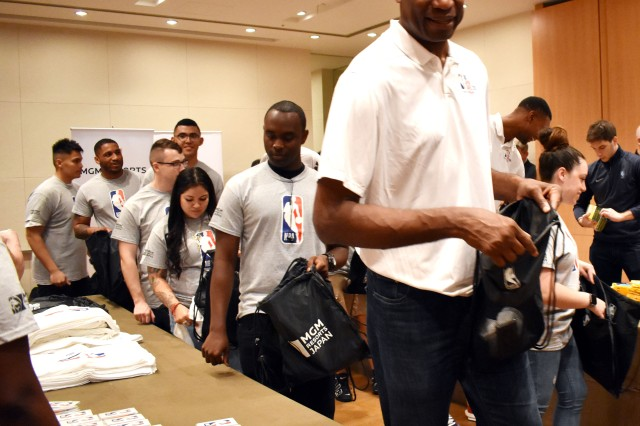 """Dikembe Mutombo, right, who played 18 seasons in the NBA, works with Camp Zama Soldiers to make """"NBA Cares"""" packages for orphans and remotely stationed Soldiers at the Grand Hyatt Tokyo, Japan, Oct. 6."""