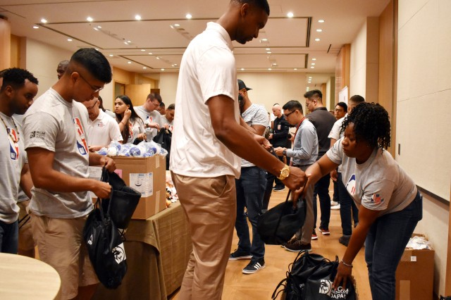 """Chris Bosh, who played 13 seasons in the NBA, hands  a care package to Sgt. Michelle Wade, a member of Better Opportunities for Single Soldiers at Camp Zama, after Soldiers and NBA legends teamed up to create """"NBA Cares"""" packages for orphans and remotely stationed Soldiers at the Grand Hyatt Tokyo, Japan, Oct. 6."""