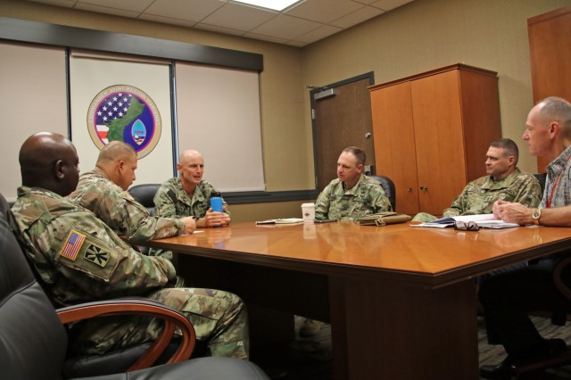 Col. Patrick M. Costello, 38th Air Defense Artillery Brigade commander, Command Sgt. Maj. Neil Sartain, 38th ADA Brigade senior enlisted advisor; Maj. Bryan Z. Lipe, Task Force Talon officer in charge; and Sgt. Maj. Dennis M. Petty, TF Talon senior enlisted advisor, meet with U.S. Navy Capt. Han Sholley (center), Joint Region Marianas chief of staff, and Dr. Michael J. Paulovich, JRM executive director, to discuss communication capabilities and future multi-domain training to enhance interoperability throughout the Indo-Pacific Region, Oct. 8. Sgt. Raquel Villalona