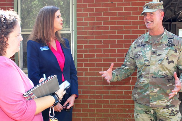 Col. Whitney B. Gardner, Fort Rucker garrison commander, speaks with a local reporter as Melissa Bryson, Corvias operations director, looks on, during a tour of a home renovation in the Munson Heights neighborhood on post Oct. 2.