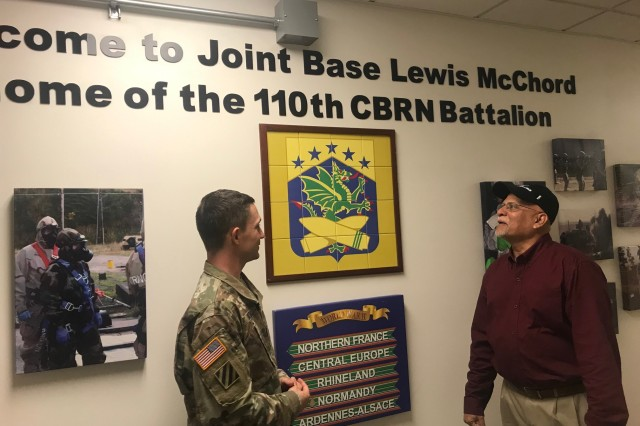 Major Brian Smith, left, 110th Chemical Battalion, 555th Engineer Brigade, and Sakhawat Amin, Joint Base Lewis-McChord's Directorate of Public Works energy program coordinator, discuss energy conservation efforts inside the 110th Chemical Battalion's building recently.