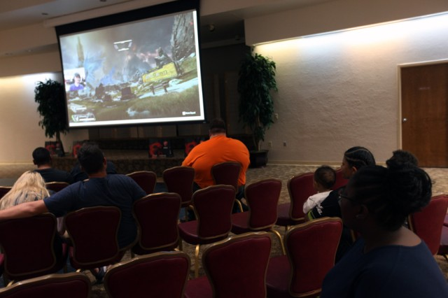 The audience watches a large screen as a professional gamer plays it from a nearby console Oct. 5, 2019, at the Patriot Club. The crowd could play against the pros and ask them questions about gaming.