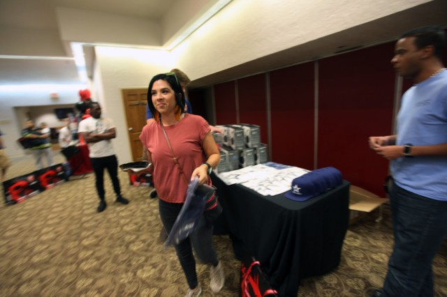 Stacy Oliver receives a T-shirt as a door prize during the open gaming session Oct. 5, 2019, at the Patriot Club. compLexity Gaming provided the prizes. Fort Sill BOSS president Sgt. Ernesto De Jesus is at the right.