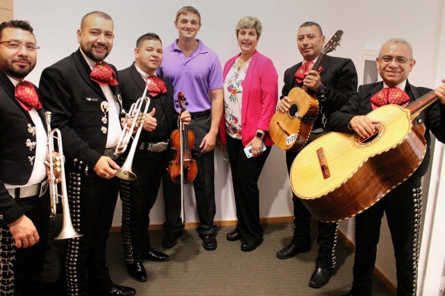 Local band Mariachi Tierra Mia poses with U.S. Army Chemical Materials Activity employees, Michael Scott and Carmen Adrover, center, during the National Hispanic Heritage Month observance event Oct. 2, 2019 at Aberdeen Proving Ground (APG), Md. Adrover is an active member of Team APG and assists each year with planning and coordinating the event. (U.S. Army photo by Jessica Tayson)