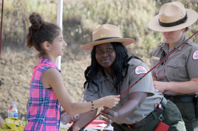 Park Ranger Antoinette Patterson hands out fishing poles during Kid's Fishing Day at the Corps of Engineer's Hensley Lake outside of Madera, California, on April 13.