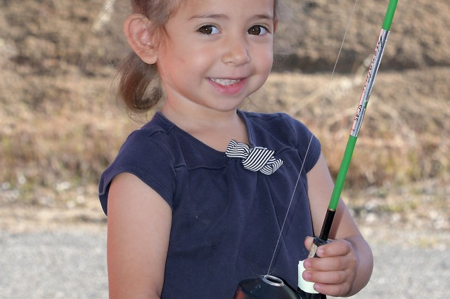 Three year old Zara grins as she accepts a fishing pole to use during Kid's Fishing Day at the Corps of Engineer's Hensley Lake outside of Madera, California, on April 13.