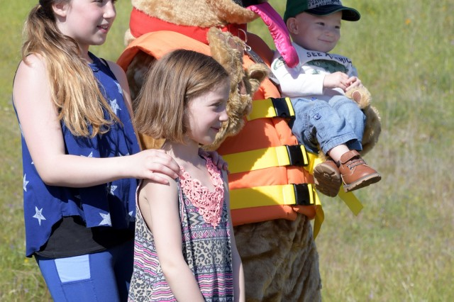 From left, Annika, 12, Ainsley, 8, and 18-month-old Liam pose for a quick photo with Bobber during Kid's Fishing Day at the Corps of Engineer's Hensley Lake outside of Madera, California, on April 13.