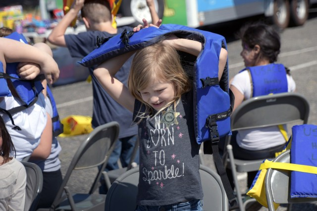 Makenza, 8, plays a version of Musical Chairs that involves putting on a life jacket during Kid's Fishing Day at the Corps of Engineer's Hensley Lake outside of Madera, California, on April 13.