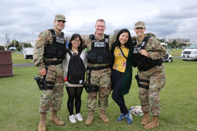 Attendees at the Fall Festival, an annual open-post event on Sagami General Depot, Japan, pose for a photos with military police officers during the event Oct. 6.