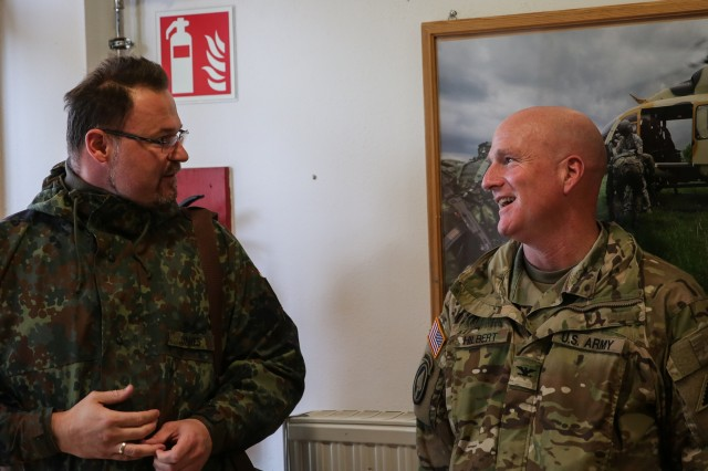 Florian Junkes, Hohenburg mayor, speaks with Col. Joseph Hilbert, commander of Operations Group for Joint Multinational Readiness Center, before Observer Coach/Trainer teams from JMRC took the Mayors from the local surrounding communities on a helicopter tour of the Hohenfels training area on Oct. 8.