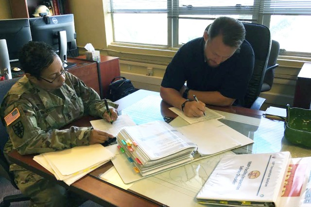 835th Sgt. 1st Class Sandra Esquivel, cargo specialist, goes over records with 599th safety officer, Rob Brenckle, during an inspection on Sept. 23.