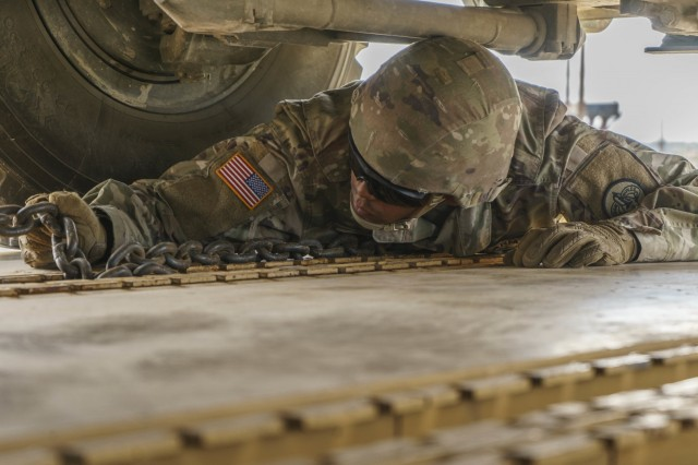 Pvt. Isaiah Montes, assigned to Field Artillery Squadron (Steel), properly secures chains to the rail cart before attaching it to a M1126 Stryker vehicle during railhead operations, Oct. 7, at Fort Hood as part of preparation for the 3rd Cavalry Regiment's rotation to the National Training Center. (U.S. Army photo by: Staff Sgt. Justin Geiger, 3rd Cavalry Regiment Public Affairs)