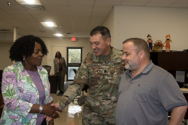 Command Sgt. Maj. Mario Terenas (center), command sergeant major for Fort Knox and U.S. Army Cadet Command, hands Wendy Cherry, Director of Finance, a Fort Knox challenge coin Oct. 8, 2019.