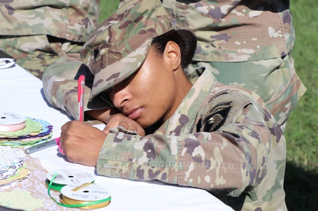 2018 Footprints on the Heart participant Spc. Kearra Murry, assigned to the 96th Aviation Support Battalion, 101st Combat Aviation Brigade, writes a note on an ornament in remembrance of her angel baby. Murry and others participated in the annual remembrance held at Blanchfield Army Community Hospital Oct. 18, 2018, in conjunction with National Pregnancy and Infant Loss Awareness Month. U.S. Army photo by Maria Yager.